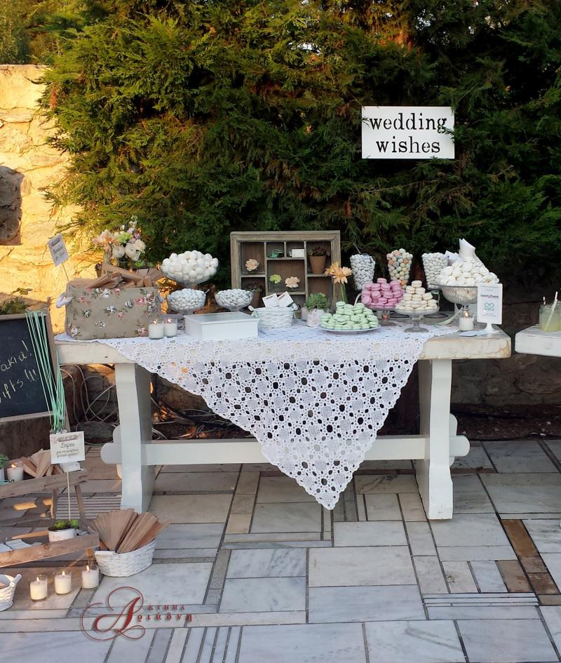 Vintage τραπέζι ευχών στρωμένο με δαντελένιο πλεκτό τραπεζομάντιλο και γεμάτο με γλυκίσματα και πολύχρωμα μακαρόν