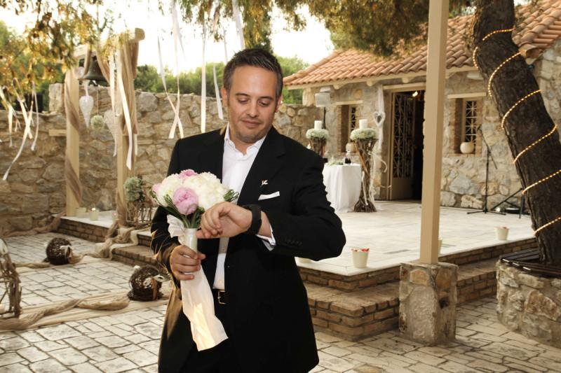 Ο γαμπρός ανυπομονεί περιμένοντας τη νύφη και κοιτάζει το ρολόι του.
