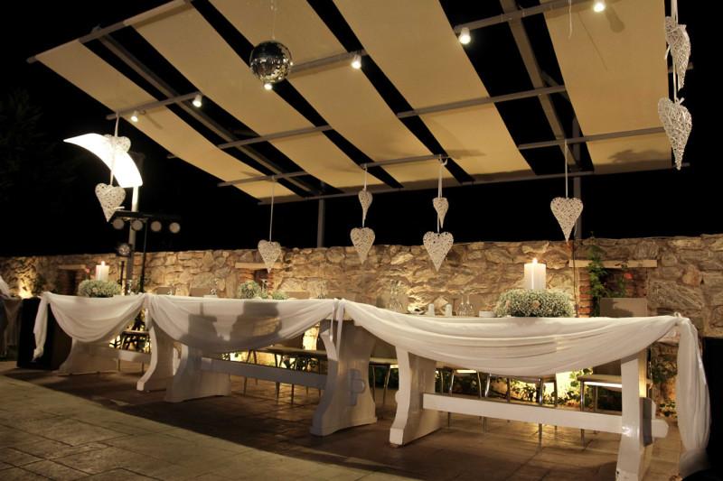 Το νυφικό τραπέζι που αποτελείται από μοναστηριακού ύφους λευκά τραπέζια και είναι διακοσμημένο ρομαντικά με υφάσματα, κεριά και ανθοσυνθέσεις