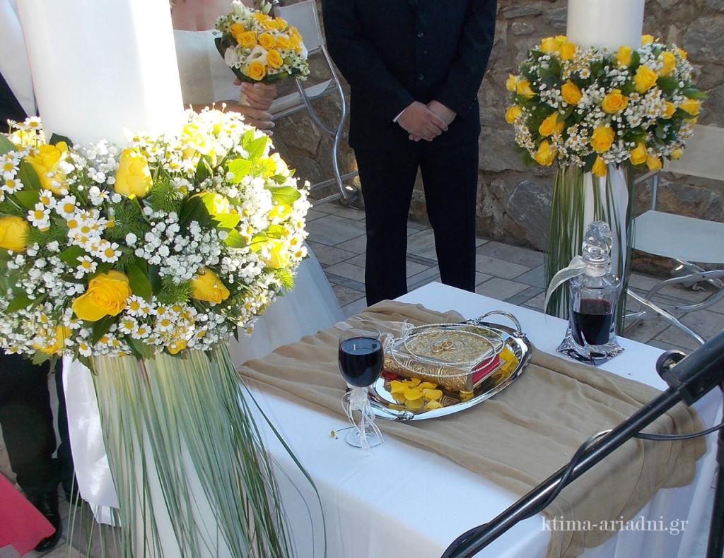 Οι λαμπάδες γάμου στολισμένες με λευκά και κίτρινα λουλούδια, ακολουθούν το στυλ και τα χρώματα του υπόλοιπου στολισμού. Το κίτρινο χρώμα ταιριάζει πολύ και με την λινάτσα που επιλέχθηκε ως το ύφασμα για τον στολισμό διάφορων σημείων