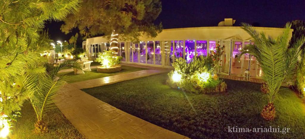 Είναι βράδυ στο κτήμα Αριάδνη. Στεκόμαστε έξω από την αίθουσα του χώρου Φαιστός στο κτήμα Αριάδνη και απολαμβάνουμε τα χρώματα που αλλάζουν εντός της, χάρη στον φωτισμό, όσο το γαμήλιο πάρτυ συνεχίζεται και το κέφι μεγαλώνει