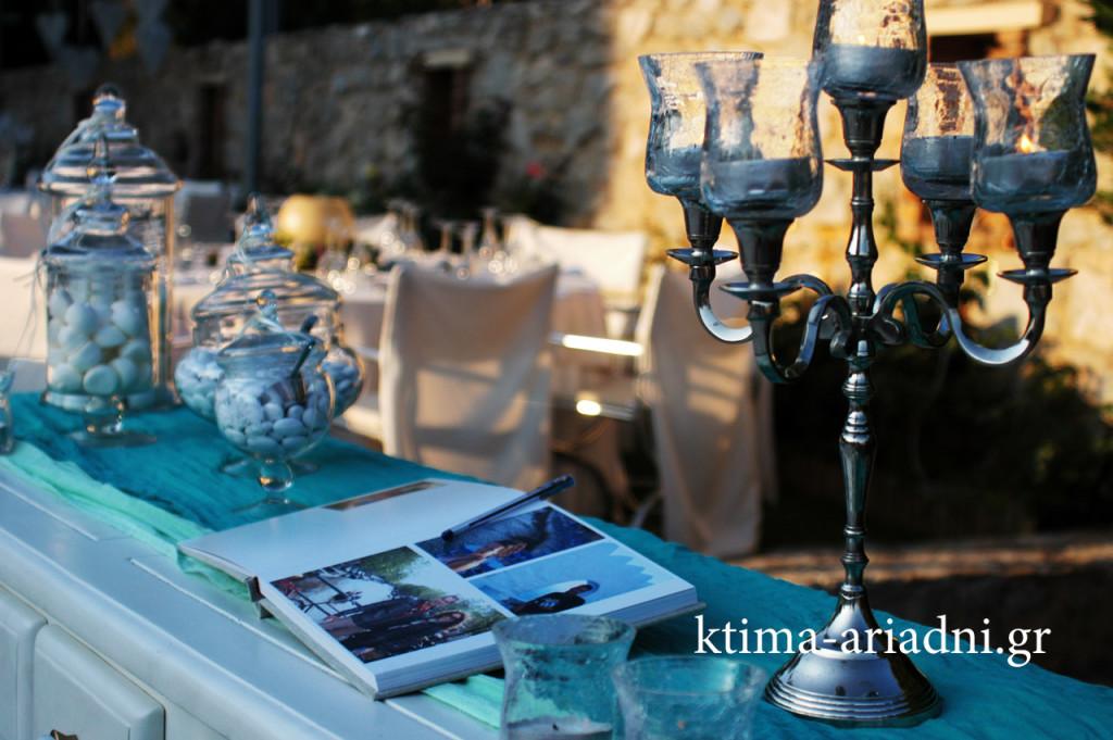 """Το """"τραπέζι"""" με το βιβλίο ευχών ήταν ο λευκός vintage μπουφές του κτήματος, διακοσμημένος με κηροπήγια και γυάλες με κουφέτα και κεράσματα"""