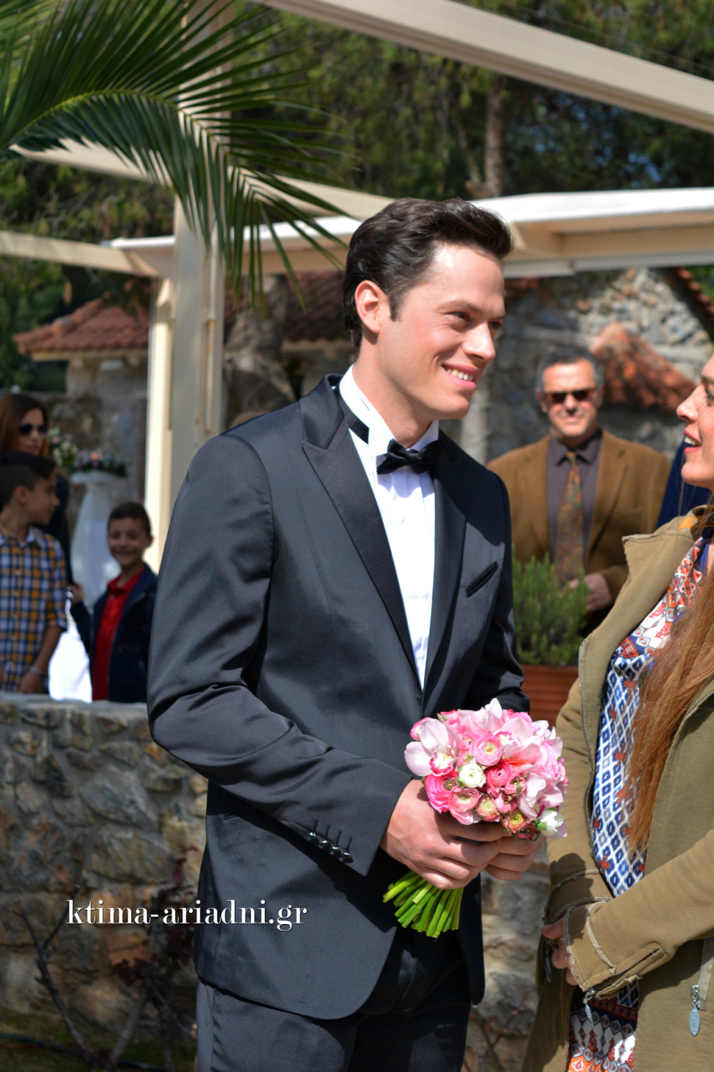 Ο γαμπρός κρατά ένα υπέροχο νυφικό μπουκέτο και περιμένει από στιγμή σε στιγμή τη νύφη