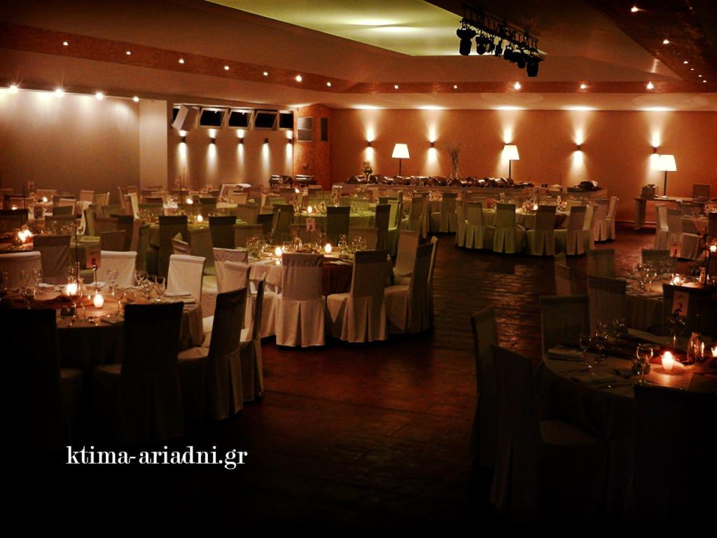 Η αίθουσα έχει ήδη ρομαντική ατμόσφαιρα χάρη στον φωτισμό και τα κεριά που άναψαν στα τραπέζια. Στο βάθος έχει στηθεί και ο μπουφές που θα ανοίξει αμέσως μετά την είσοδο του ζευγαριού