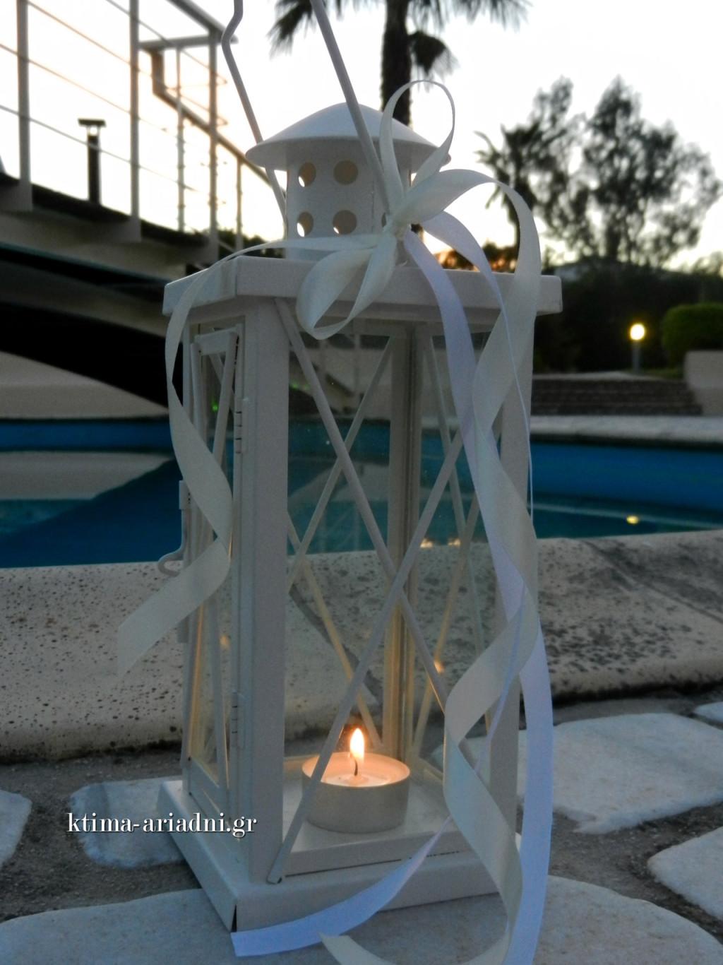 Λευκά φανάρια με λευκές κορδέλες διακοσμούσαν περιμετρικά την πισίνα και τόνιζαν το καμπυλόγραμμο σχήμα της