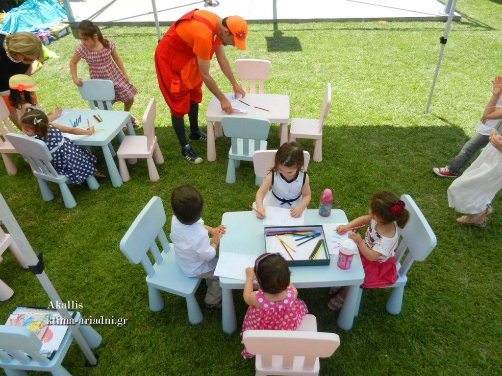 Κάτω από τη σκιά της τέντας, στα μικρά τραπεζάκια τα παιδιά περνούν όμορφα και διασκεδαστικά υπό την επίβλεψη και καθοδήγηση των επαγγελματιών
