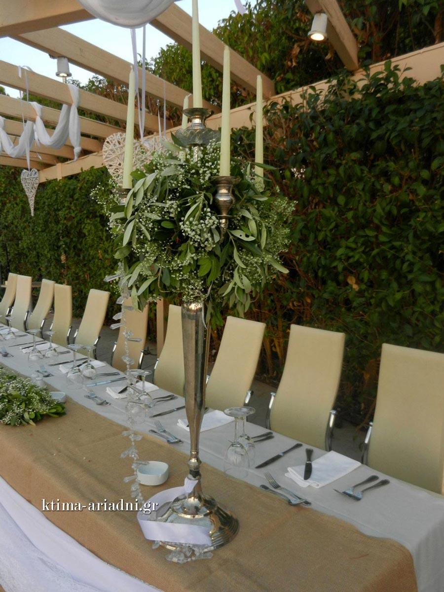 Λεπτομέρεια από την κομψή διακόσμηση στο νυφικό τραπέζι με τα ψηλά κηροπήγια.