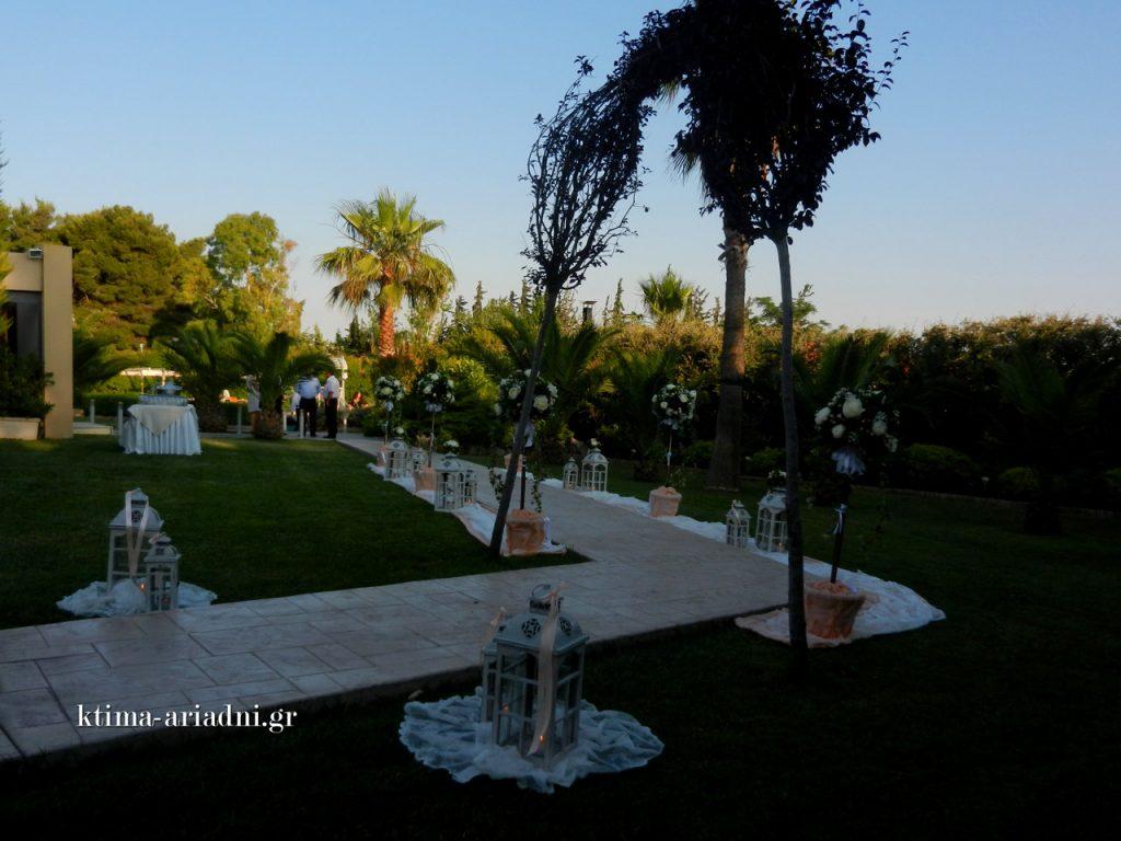 Ο καταπράσινος κήπος έξω από την εκκλησία του Αγίου Γεωργίου στον χώρο Κνωσσός του κτήματος Αριάδνη διακοσμήθηκε ρομαντικά με λουλούδια και κεριά. Μεγάλα, λευκά φανάρια και γλάστρες με ψηλές ανθοσυνθέσεις στόλιζαν τον διάδρομο.