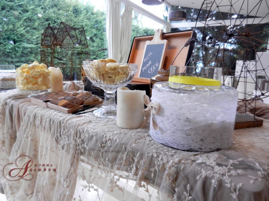 Οι λεπτομέρειες στο κέντημα του υφάσματος που καλύπτει το τραπέζι και οι δαντέλες που ντύνουν τις γυάλες με τα κουφέτα και τα γλυκά τονίζουν την επιστροφή σε μια όμορφη περασμένη εποχή