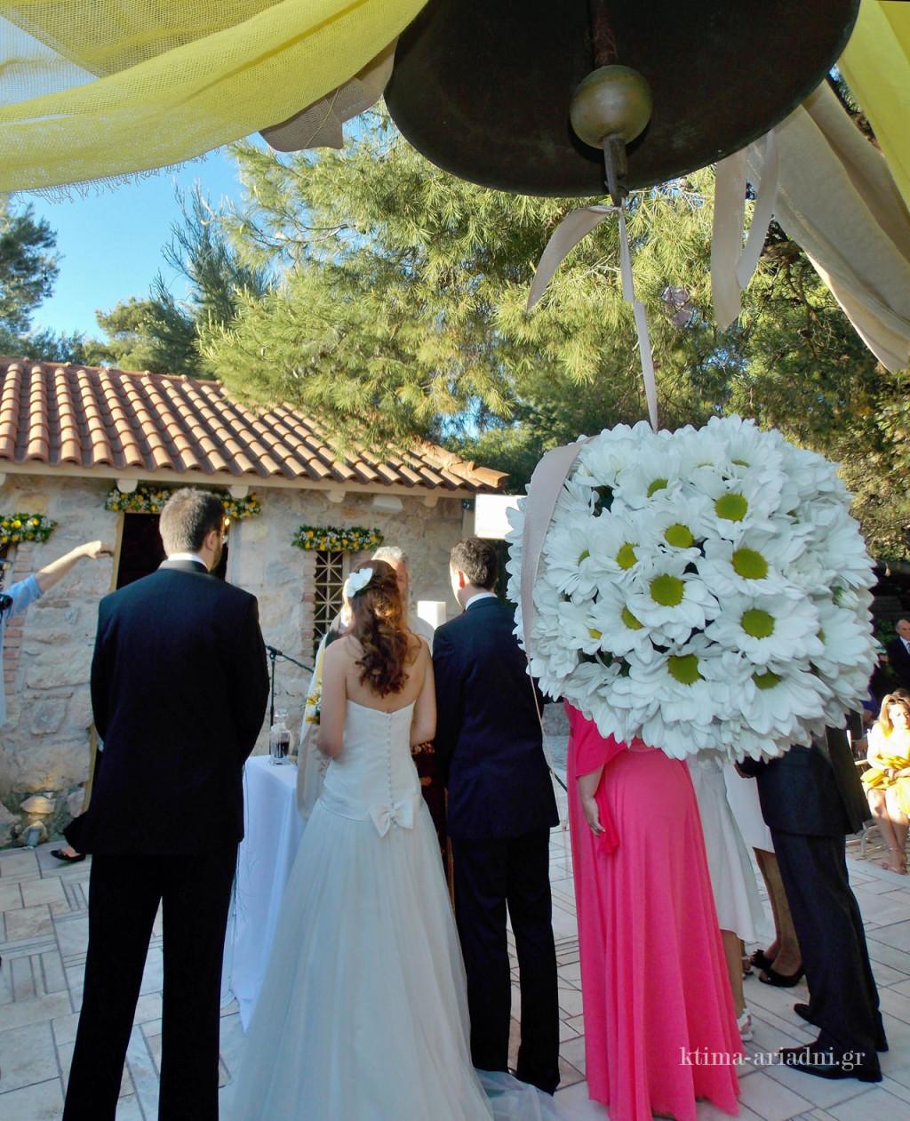 Μια λουλουδένια μπάλα από μαργαρίτες κρέμεται από την καμπάνα και προσθέτει μια ακόμα χαρούμενη πινελιά στον χώρο