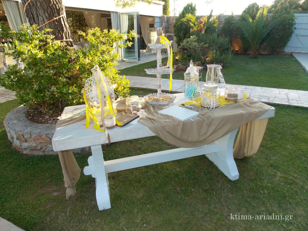 Ένα από τα λευκά, μοναστηριακού στυλ τραπέζια μας, στολισμένο με λινάτσα και αντικείμενα σε λευκό και κίτρινο, φιλοξενεί κεράσματα, κουφέτα και το βιβλίο ευχών της Πηνελόπης και του Βασίλη και φυσικά του Ορέστη