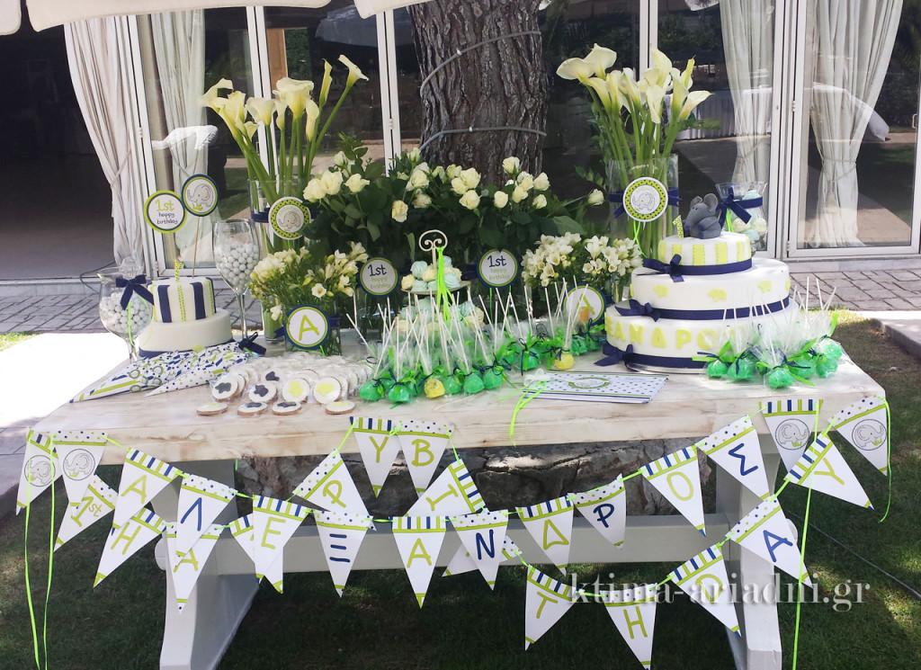 """Δεν είναι το πιο εντυπωσιακό τραπέζι με τα οποίο θα μπορούσε ο Αλέξανδρος και οι γονείς του να υποδεχθούν τους καλεσμένους τους; Στολισμένο με λουλούδια και γιρλάντες και γεμάτο με γλυκά, φιλοξενεί το βιβλίο ευχών, που είναι ασορτί με το θέμα """"ελεφαντάκια"""" και την τριώροφη τούρτα για τα πρώτα γενέθλια του Αλέξανδρου."""