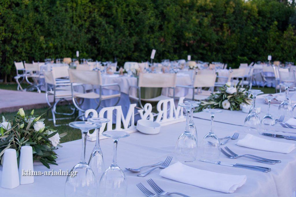 Το ξύλινο Mr & Mrs στολίζει διακριτικά το νυφικό τραπέζι, ενώ λουλούδια και φαρδιές κορδέλες στο χρώμα της ελιάς συμπληρώνουν τη διακόσμηση