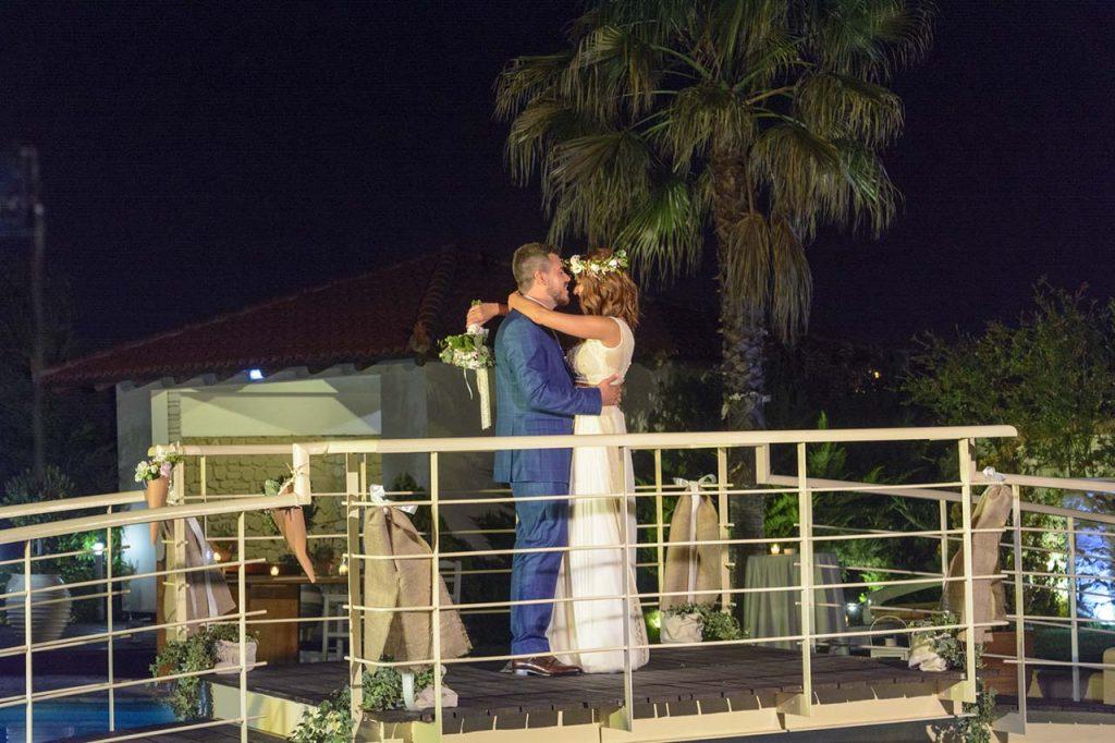 Οι νιόπαντροι χορεύουν τον πρώτο χορό στο γεφυράκι πάνω από την πισίνα