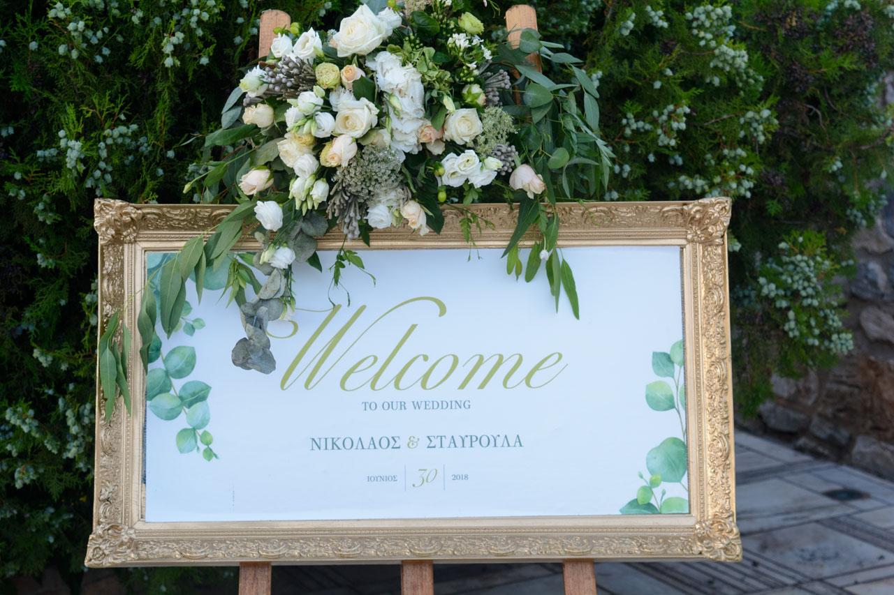 Χρυσή κορνίζα που υποδέχεται τους καλεσμένους στον γάμο του ζευγαριού στο κτήμα Αριάδνη
