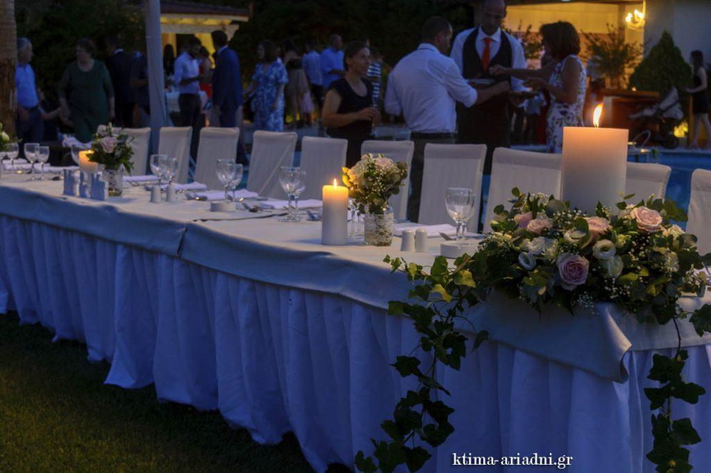 Νυφικό τραπέζι και στο φόντο οι καλεσμένοι που καταφθάνουν για τη δεξίωση